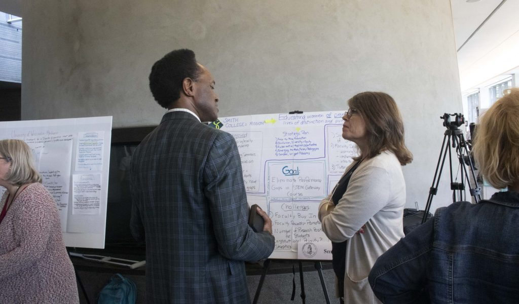 Man and woman talking in front of a posterboard